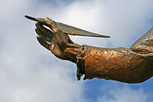 A closeup of a bronze statue, showing a hand holding a quill.
