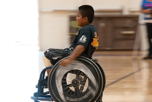 A young child zooming across a gym floor in a sports wheelchair.