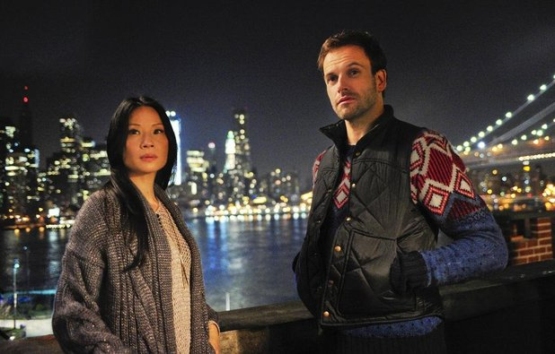 The stars of Elementary stand near the Brooklyn Bridge at night.