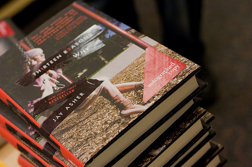 A stack of copies of Jay Asher's THIRTEEN REASONS WHY