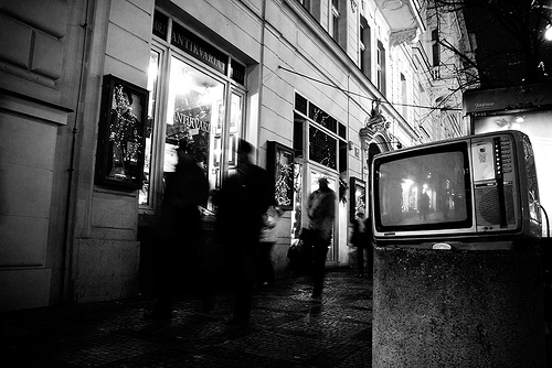 A black and white photo of a television sitting on a sidewalk, with blurred passers-by in the background.