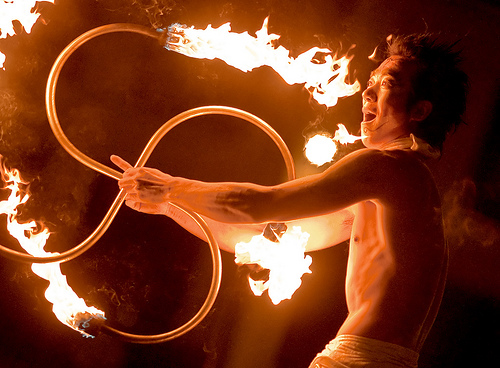 A man demonstrating poi, fire glowing as he rotates his hands.
