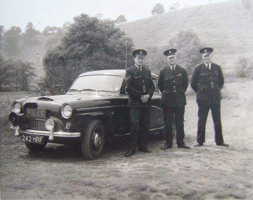 A historic photograph of three police officers and their car.