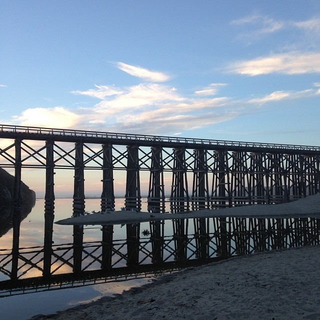A trestle bridge spanning a beach at dusk.