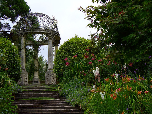 A flight of stairs leading up to a decaying garden pergola. The whole scene is filled with colourful flowers.