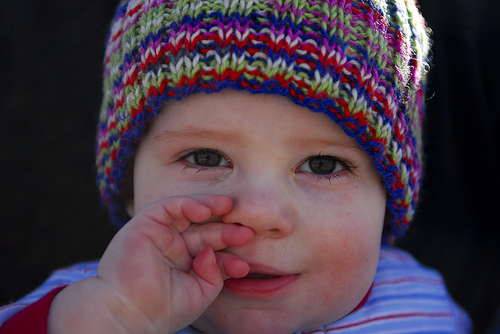 A baby, posed with hand to nose and a curious expression.