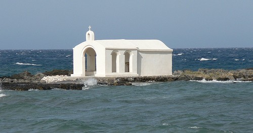 A Greek church sitting alone on a small island.