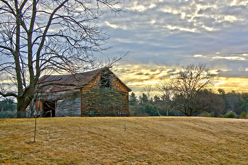 A barn at what appears to be dusk, clouds parting overhead.