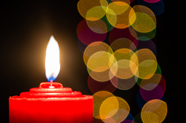 A candle burning in the dark, creating distinctive lens flares.