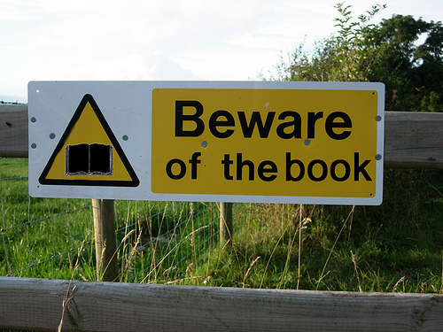 A sign warning passersby to beware of the book.