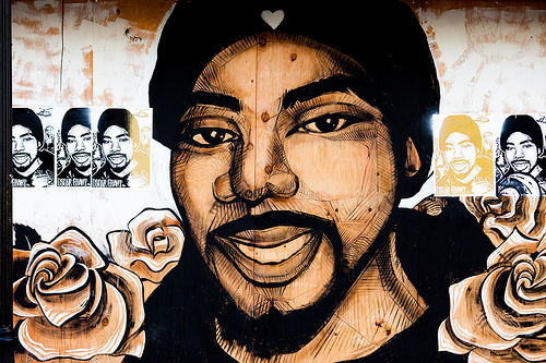 A sepia mural of Oscar Grant, surrounded by roses.