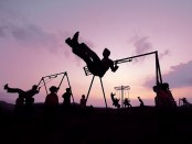 Children on swingsets at dusk.