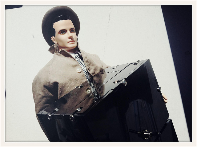 A figurine of Don Draper next to a large black box.