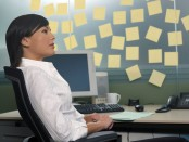 A rather hilarious stock photo of a woman seated at a computer with post-it no