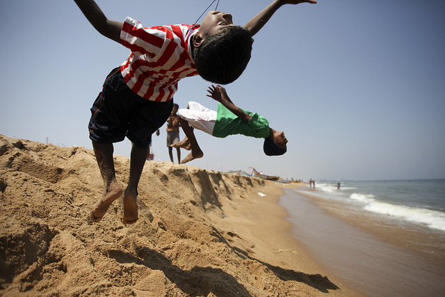 A pair of children in India taking backward leaps on a sandy beach.