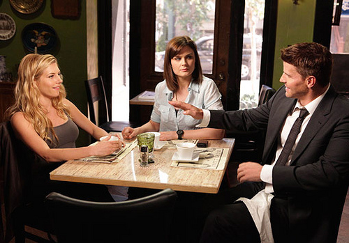 Characters Booth and Brennan from Bones sit at a cafe with Booth's then-girlfriend, a bubbly blonde.