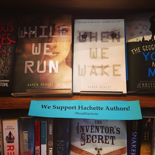 A bookshelf of titles by Hachette authors, with a supportive sign.
