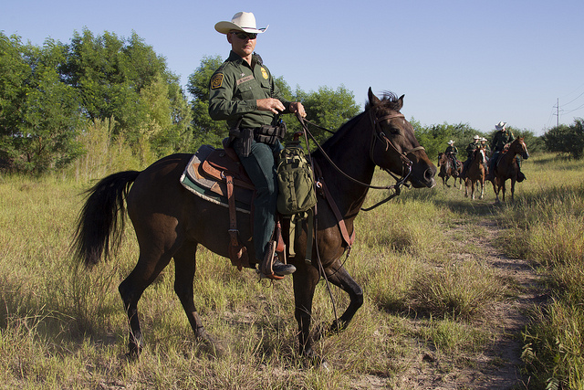 Mounted Border Patrol officers in an area of brush and scrub.