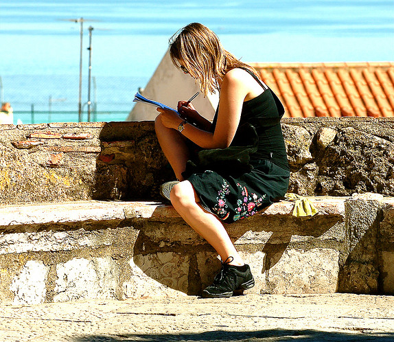 A person writing while seated on a low wall outside in the sun, tiled roofs in the background.