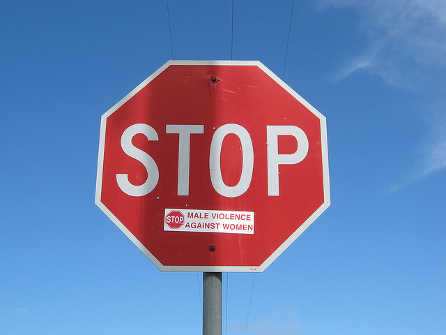 A stopsign modified to read STOP MALE VIOLENCE AGAINST WOMEN.