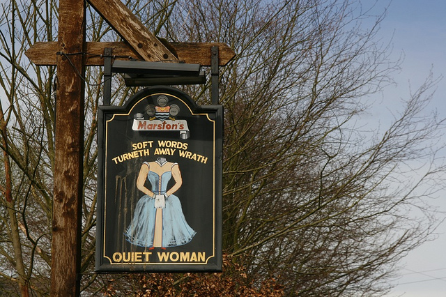 A sign advertising an inn, with a picture of a headless woman and a note: soft words turn away wrath.