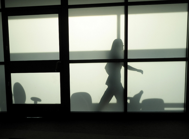 A silhouette of a hospital office viewed through frosted glass windows.