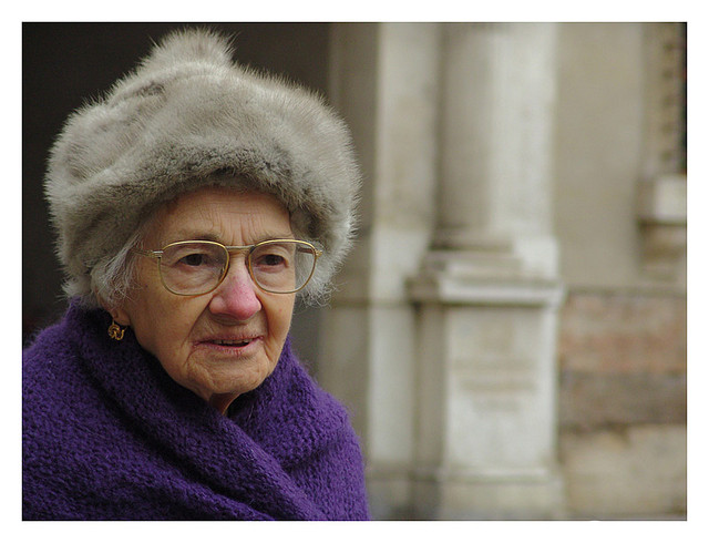 A portrait of an old woman in a purple coat and a fur hat.