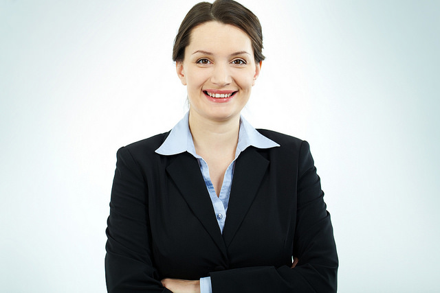 A woman in a suit, smiling.