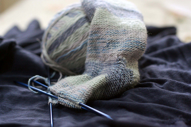 Knitting laid out on a table, showing a sock mostly completed.