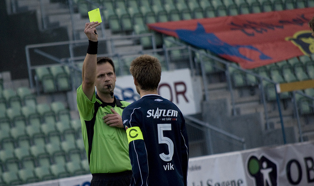 A soccer referee warning a player with a yellow card.