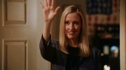 Actress Janel Moloney as Donna Moss, waving her hand