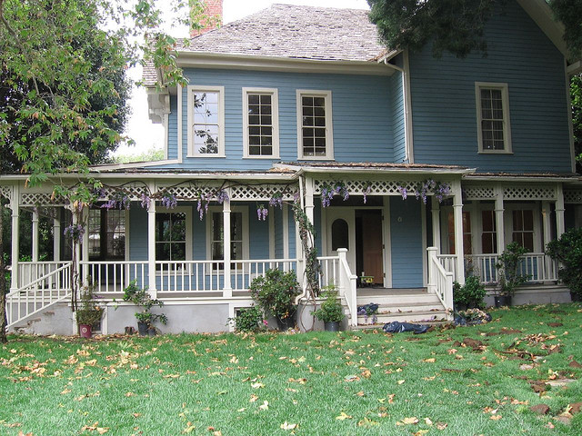 A two story white farmhouse with a wraparound porch covered in wisteria.