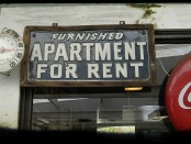 A sign advertising an apartment for rent, next to an old-fashioned Coca-Cola ad.