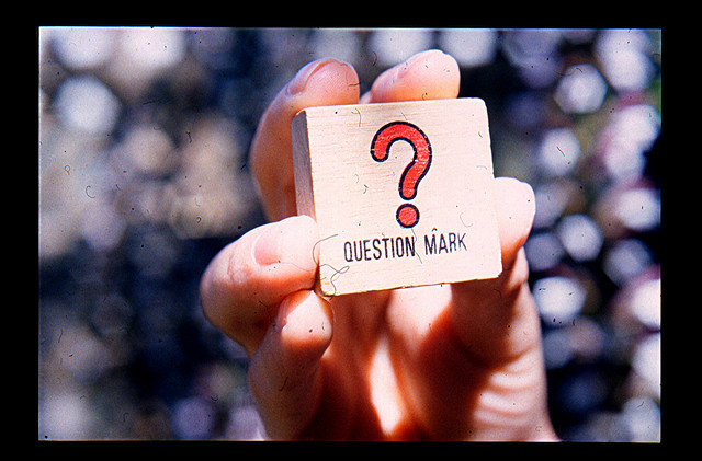 A person holding up a card with a question mark on it.