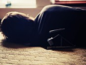 A person lying on a bed, obviously fatigued.