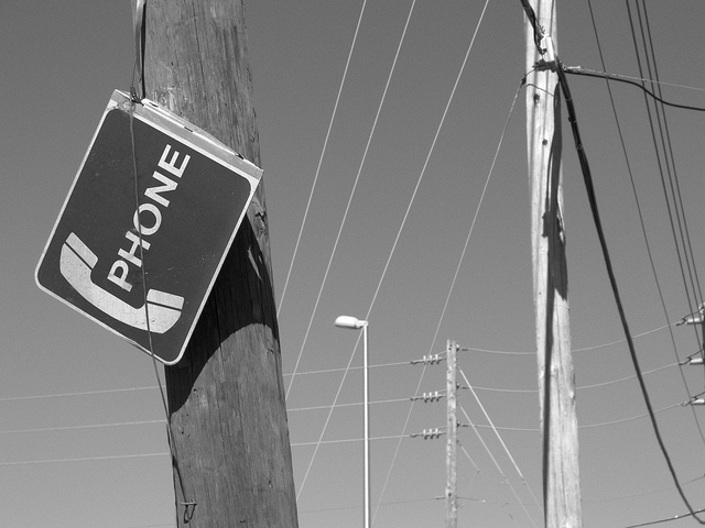 A black and white photo of phone poles and sagging wires, with a payphone sign listing in the foreground.