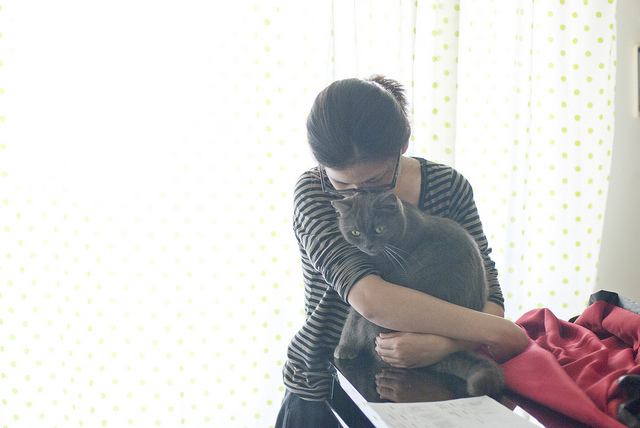 A woman hugging a grey cat.