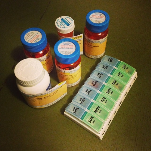 An array of medications and a pill organiser.