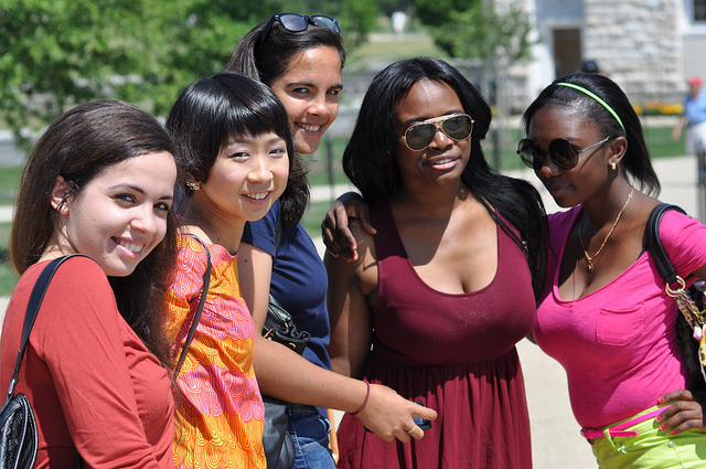A multiracial group of girls smiling in the sun.