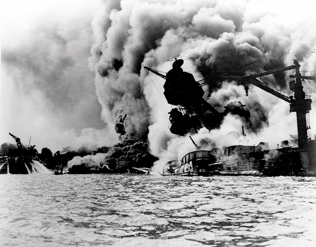 A file photo of the Pearl Harbour attack, showing a ship engulfed in flames and starting to sink.