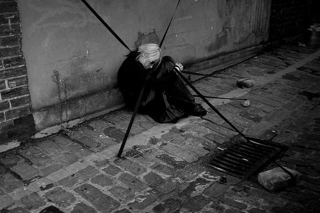 A figure in black hunched against a wall, wrapped in trailing black ribbons