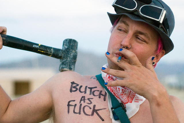 An individual wearing a helmet, holding a hammer, and smoking. Writing on the person's chest declares BUTCH AS FUCK.