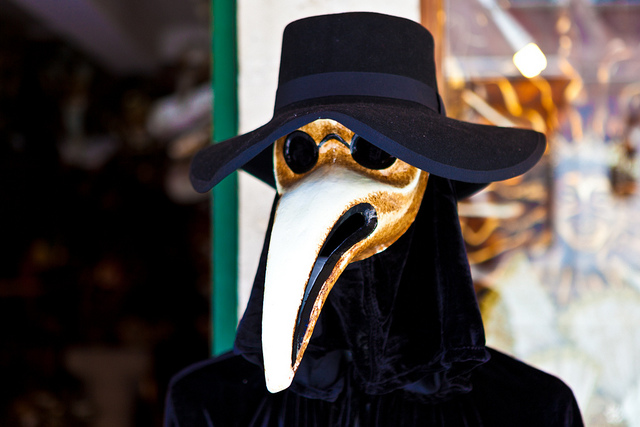 A figure dressed in a historical plague doctor mask, with the characteristic full-face covering and long beak