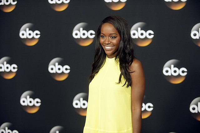 Actress Aja Naomi King at a promotional event, wearing a stunning yellow dress that contrasts elegantly with her dark skin.