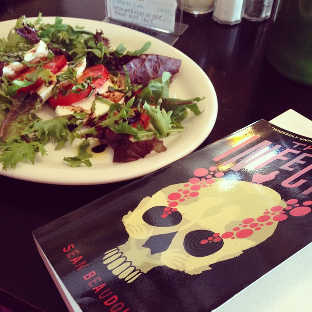My copy of THE INFECTS, sitting next to a caprese salad.