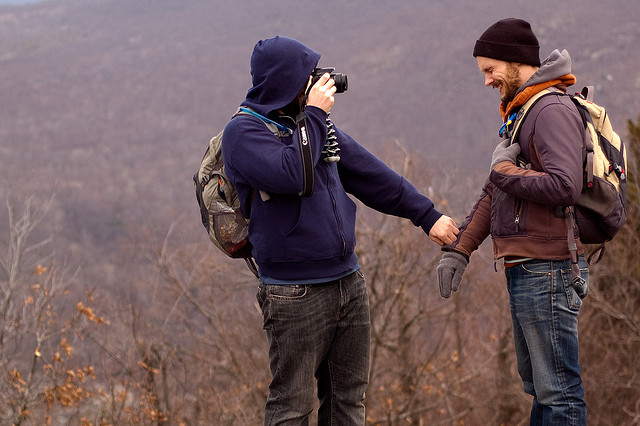 Two gay men on a foggy hillside, holding each other's hands. One is taking a photo of the other.