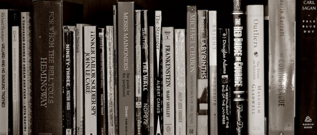 A black and white photo of a row of books.