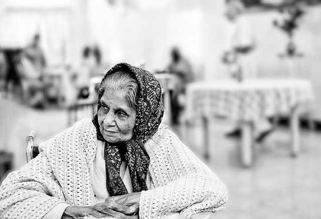 A black and white photo of an old woman wrapped in shawls.
