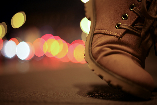 A closeup of a boot walking at night.