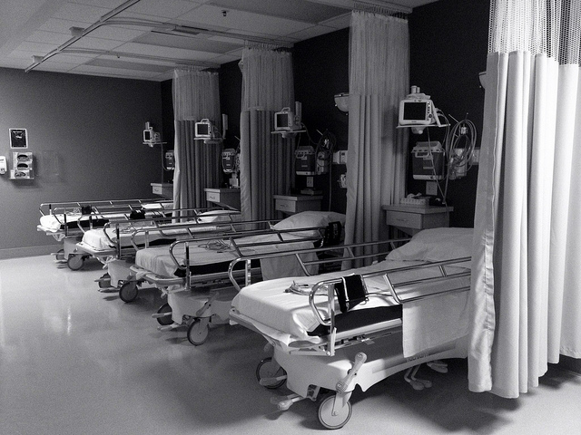Four empty hospital beds lined up